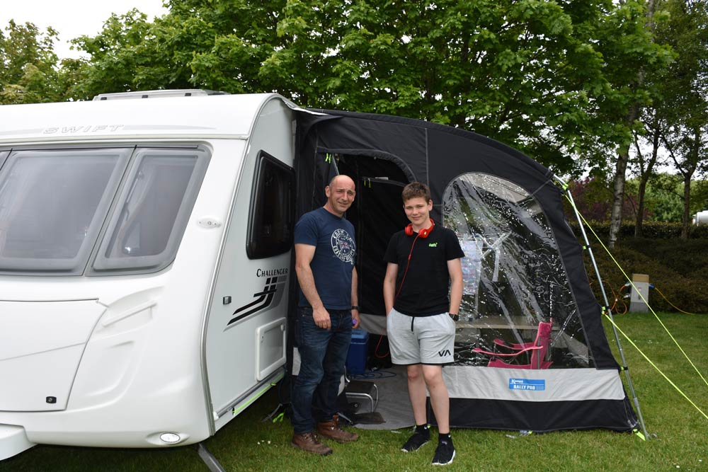 Father and son next to caravan