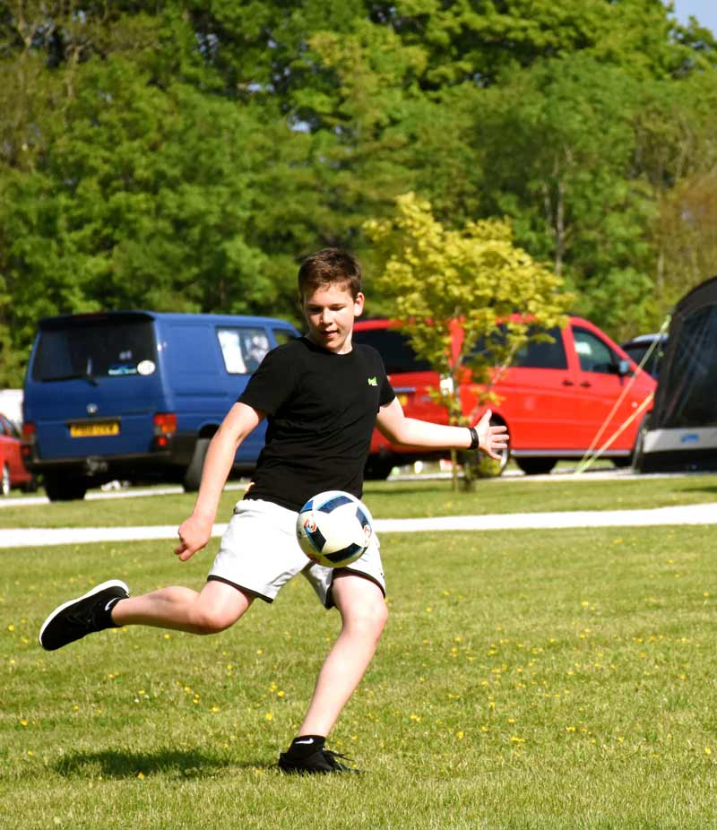 teenager playing football at campsite
