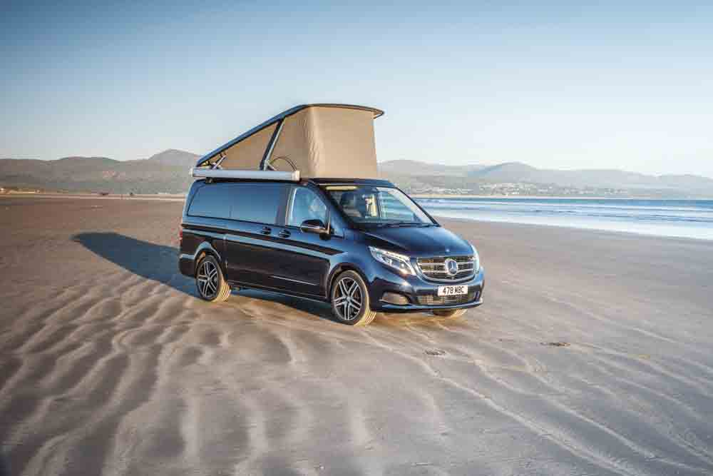 Image of a pop-top campervan on a beach
