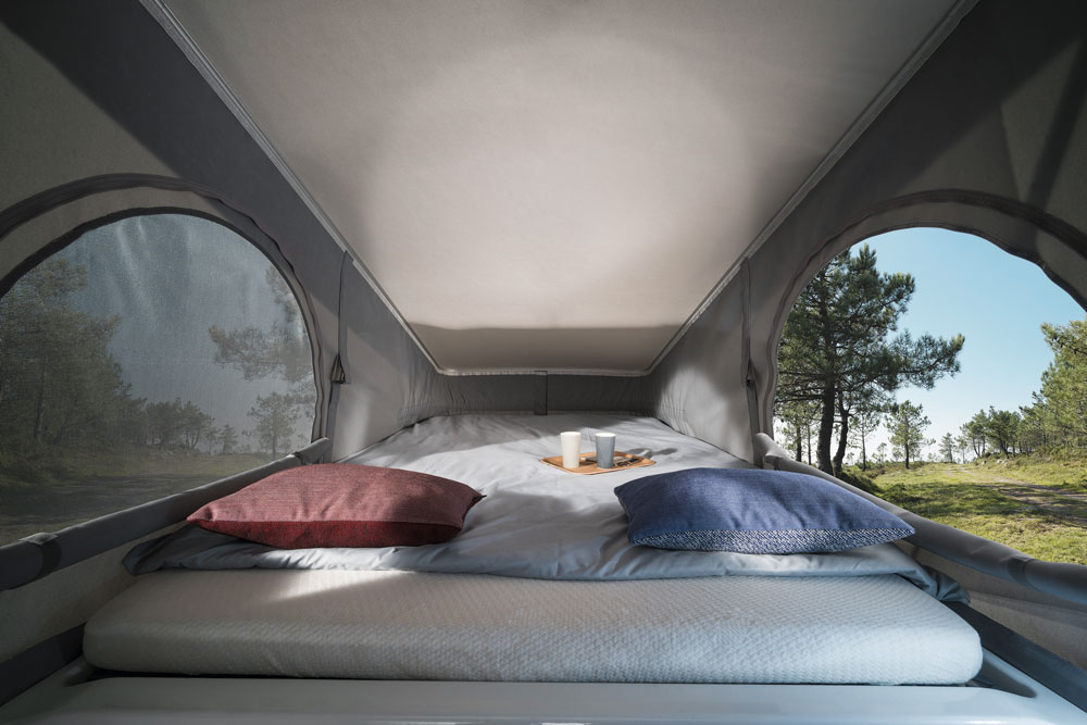 The inside of a campervan with a pop-top roof, with a bed