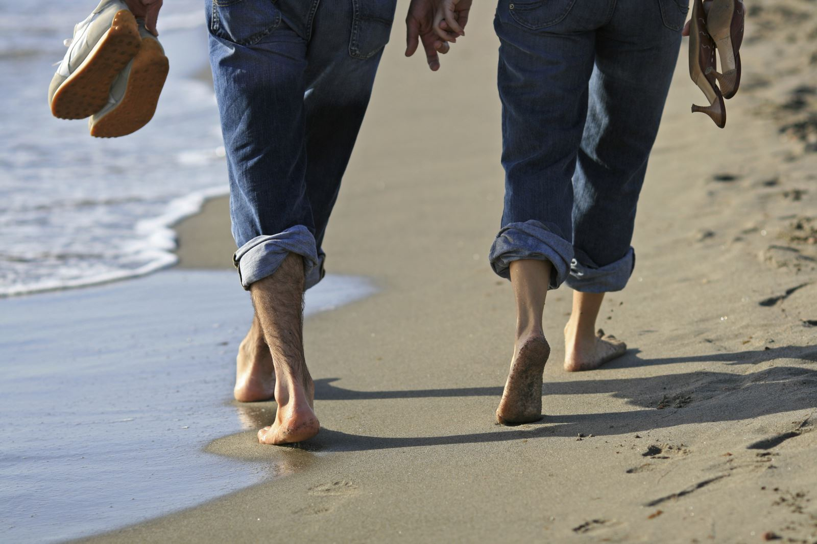 Image of a couple strolling on the beach holding hands