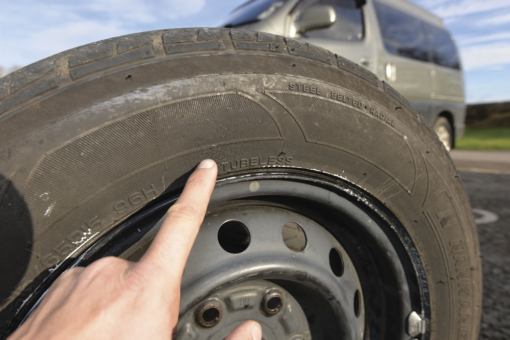Checking the tyre for any cracks or damage